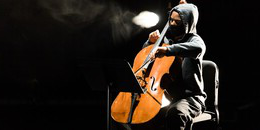 musician in a hoodie playing a cello on stage
