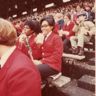 Vintage photo of student looking into camera while performing with the Penn Band