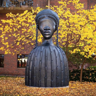 Photo of bronze sculpture surrounded by yellow foliage on Penn's campus